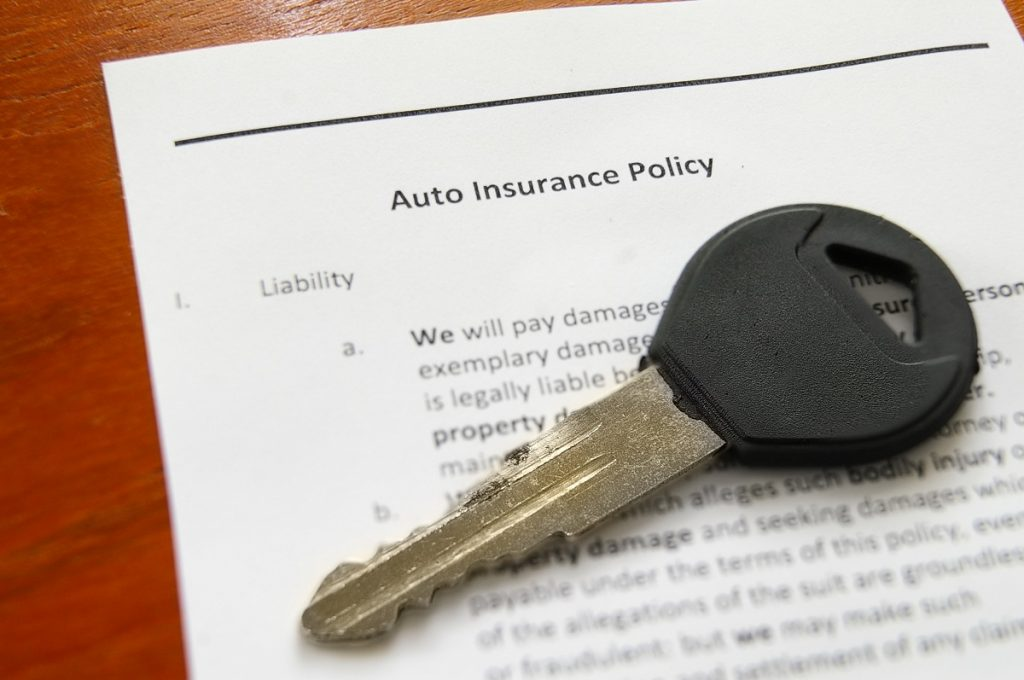 Car insurance with car key on top