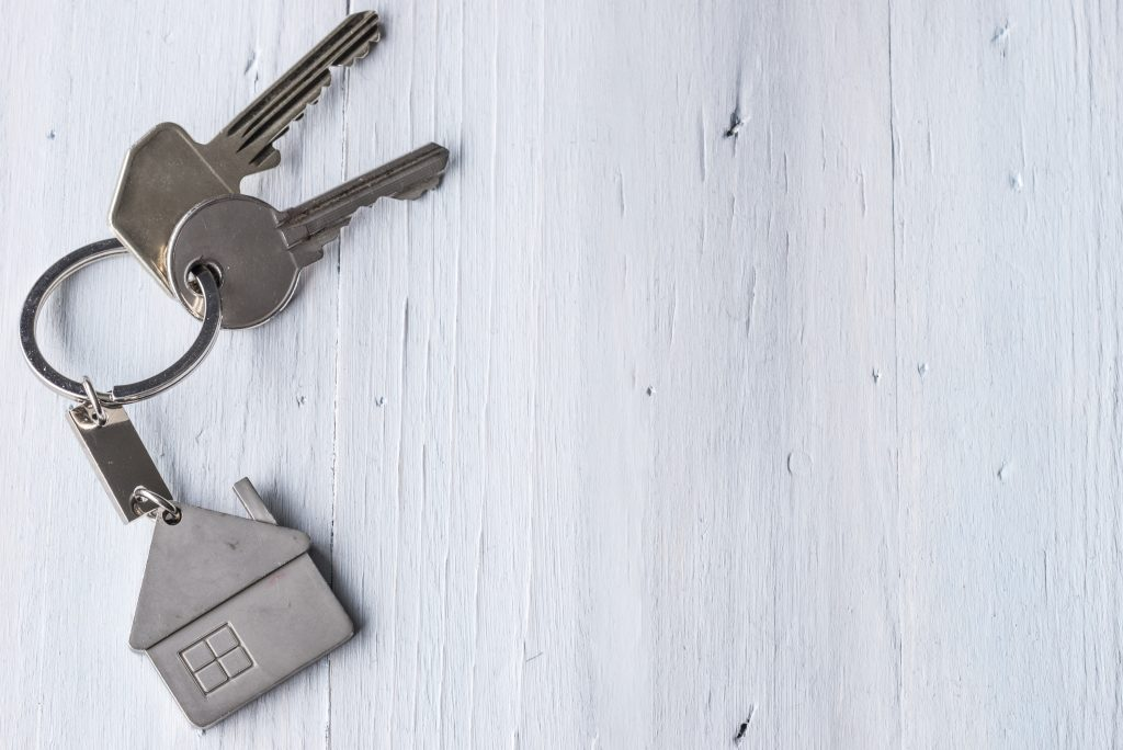 Keys with house keychain representing lease of property
