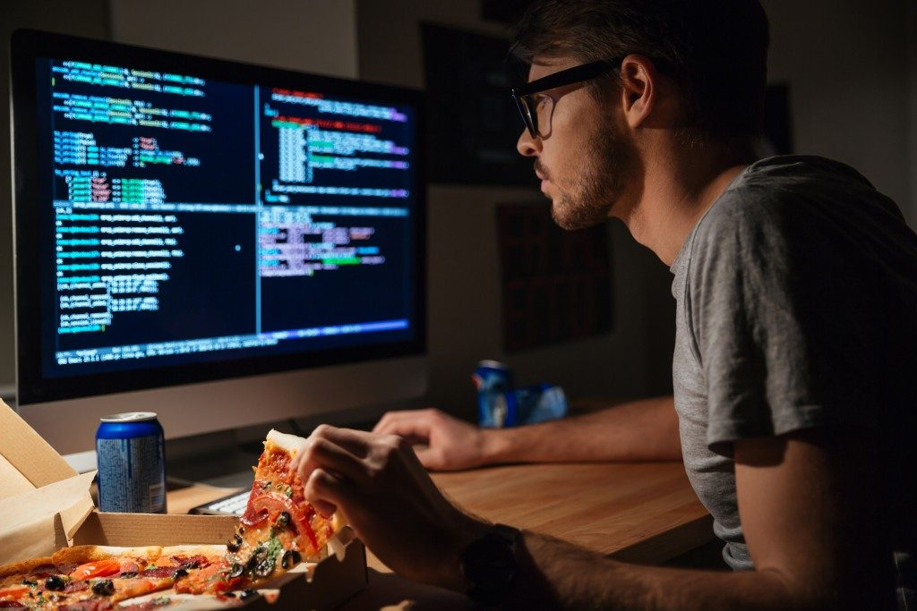 Programmer looking at codes while eating pizza