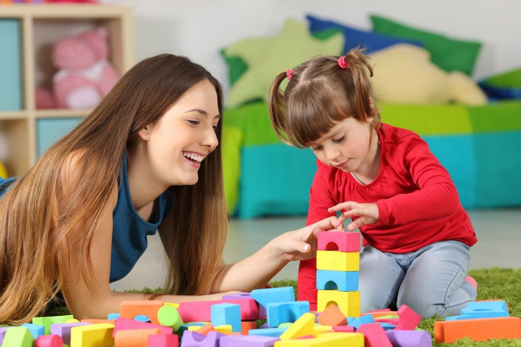 Teacher playing blocks with little girl