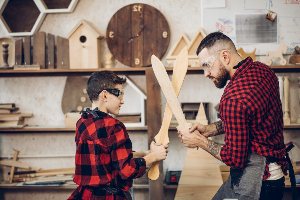 Father and child playing with handcrafted wood swords