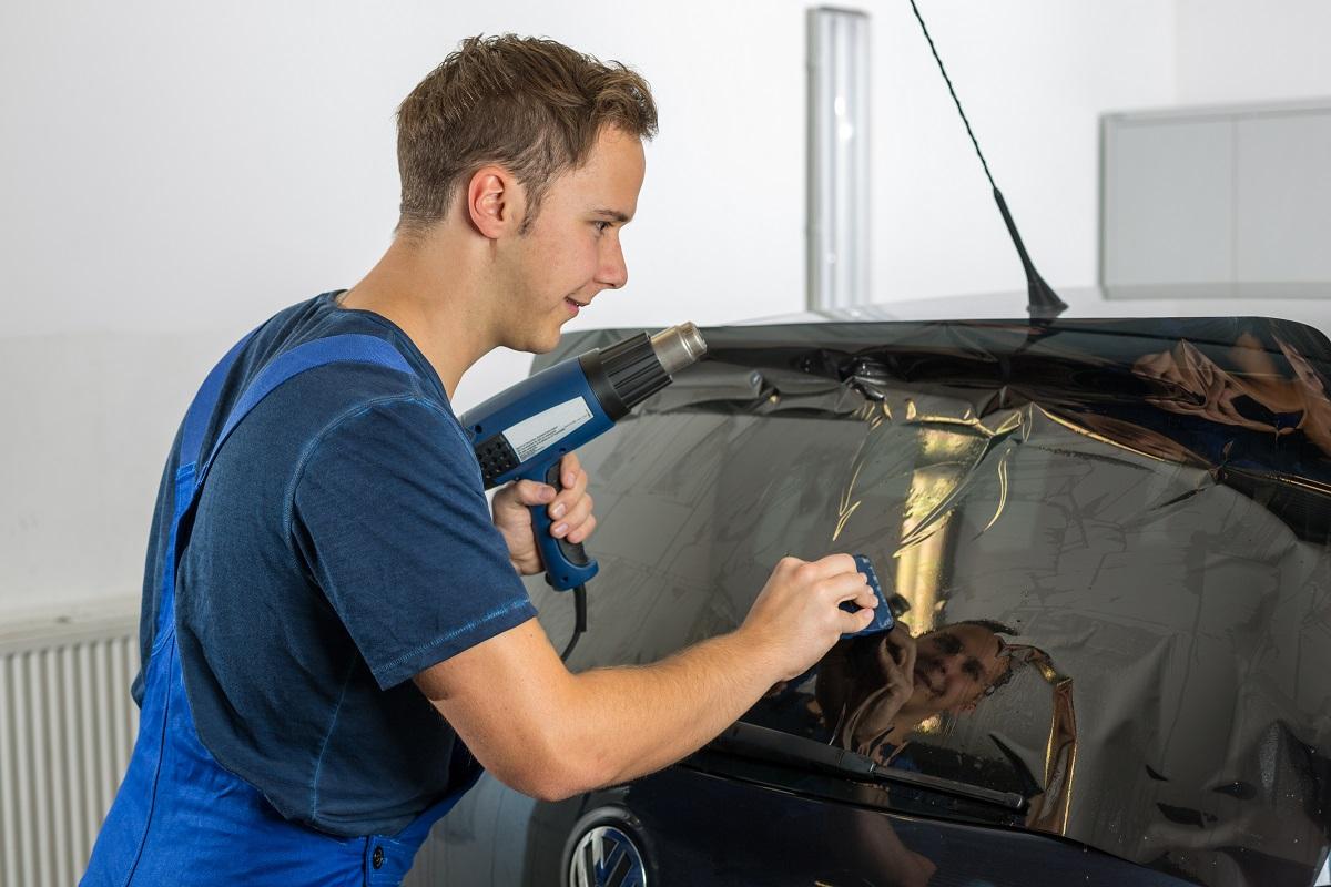 mechanic window tinting a car