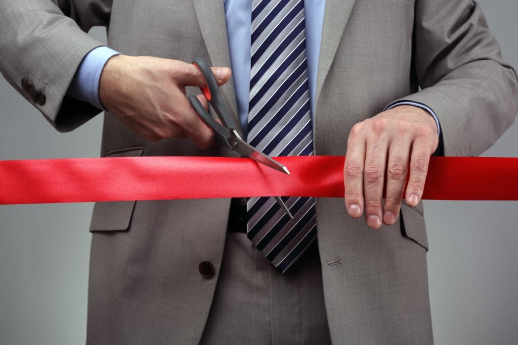 businessman cutting a red ribbon