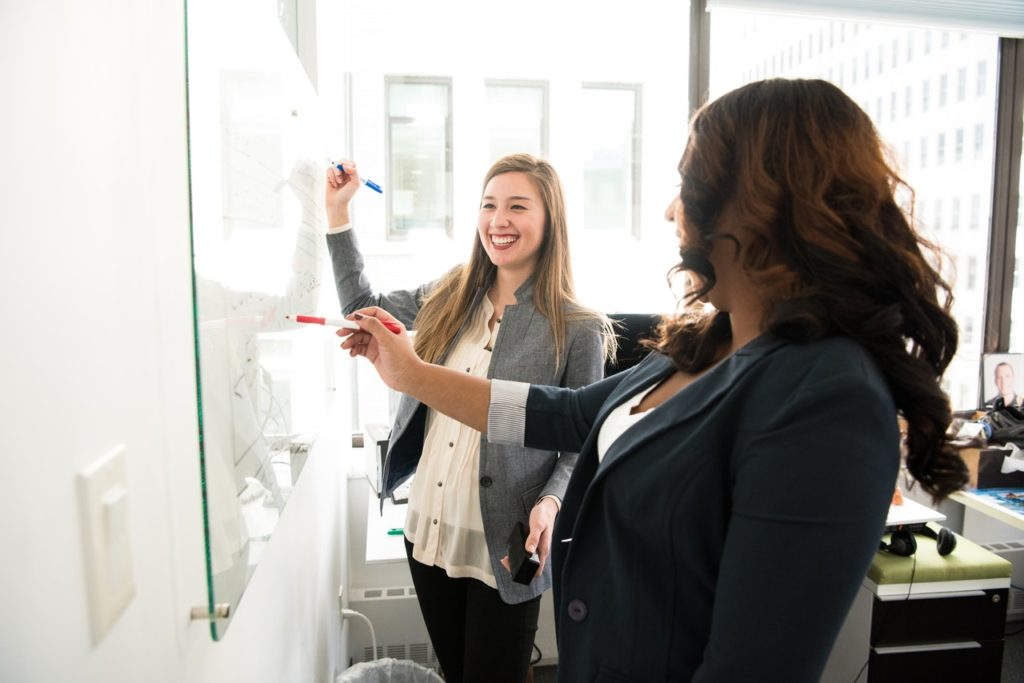 women looking at a whiteboard