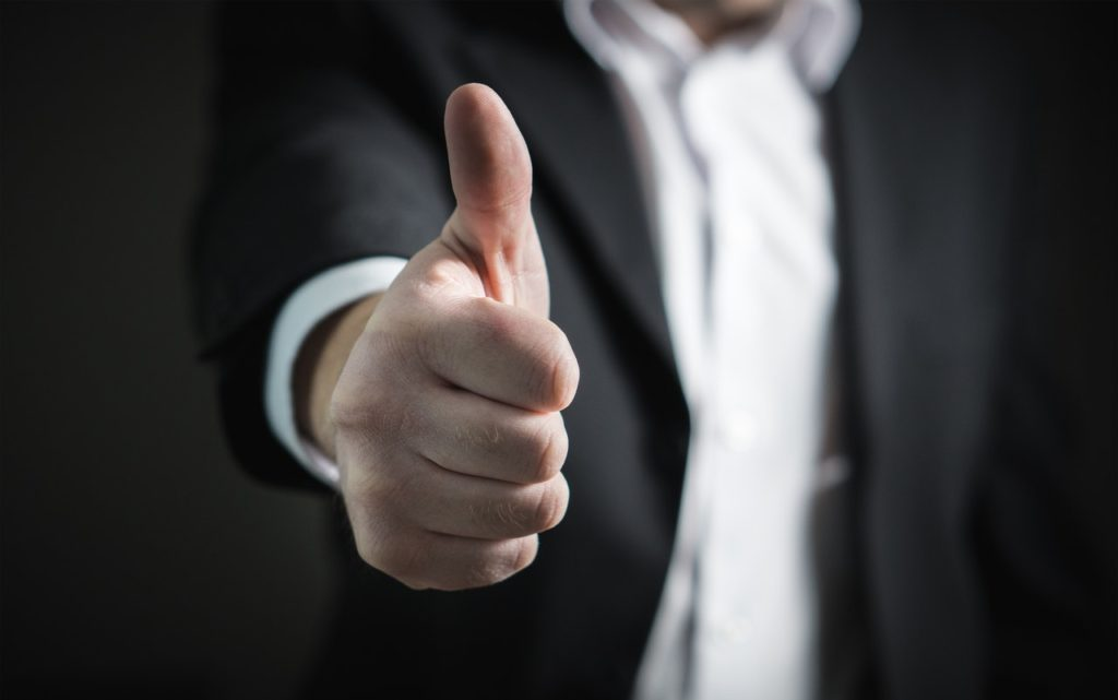 man in a suit giving a thumbs up
